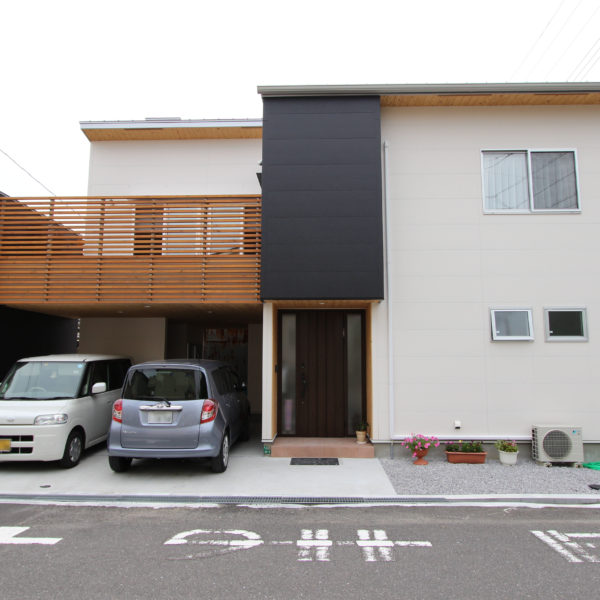 2階にLDKと広いウッドデッキを配置した住宅